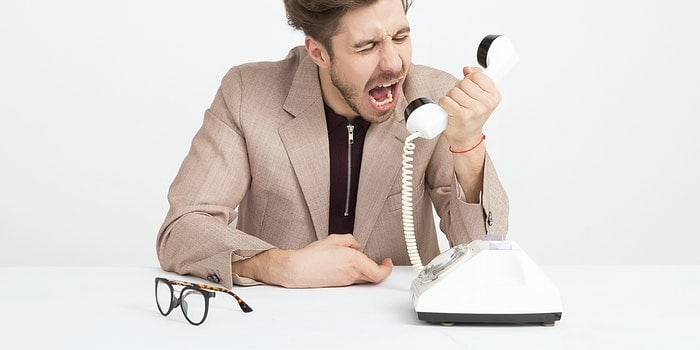 man wearing brown suit jacket mocking on white telephone 1587014 1