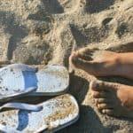 photography of a girl s feet near flip flops 1023642